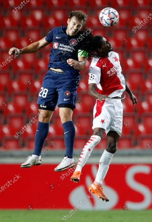Midtjylland's Erik Sviatchenko, left, challenges Slavia's Peter Olayinka during their first leg UEFA Champions League play off soccer match between Slavia Praha and FC Midtjylland at the Sinobo stadium in Prague, Czech Republic