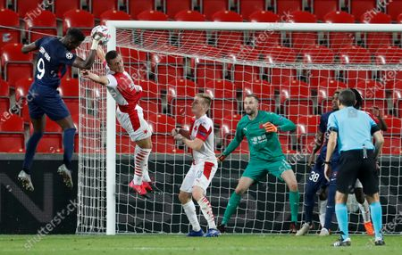 Slavia's Tomas Holes, 2nd left, challenges Midtjylland's Sony Kaba during their first leg UEFA Champions League play off soccer match between Slavia Praha and FC Midtjylland at the Sinobo stadium in Prague, Czech Republic