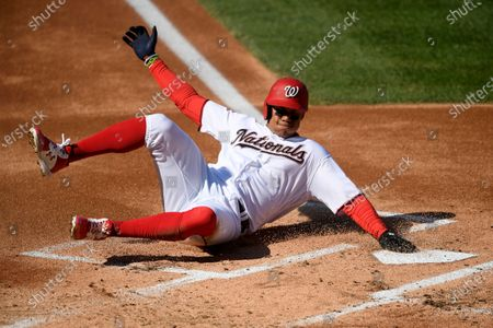 Washington Nationals' Juan Soto slides home to score on a single by Asdrubal Cabrera during the first inning of the first baseball game of a doubleheader against the Philadelphia Phillies, in Washington