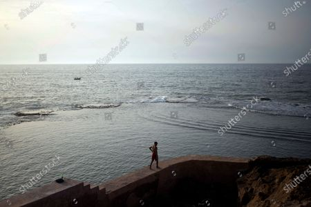 Man walks along a fence before jumping for an evening swim in the Atlantic Ocean, in Rabat, Morocco