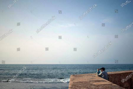 Man wearing a face mask to prevent the spread of coronavirus looks out into the Atlantic Ocean before sunset, in Rabat, Morocco
