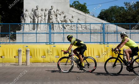 Cyclists pass the Alamo Cenotaph, in San Antonio. The Texas Historical Commission is set to decide whether to allow the restoration and relocation of the Cenotaph, a 1930s-era stone monument to Texas revolutionaries killed in the Battle of the Alamo, as part of an effort to reclaim the historical footprint of the Alamo as part of a redevelopment plan