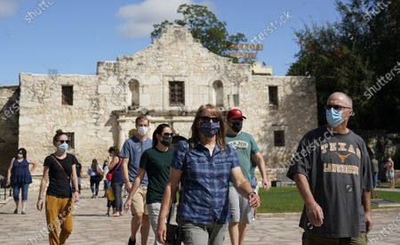 Visitors wearing masks for protection from COVID-19 leave the recently reopened Alamo, in San Antonio. The Texas Historical Commission is set to decide whether to allow the restoration and relocation of the Cenotaph, a 1930s-era stone monument to Texas revolutionaries killed in the Battle of the Alamo, as part of an effort to reclaim the historical footprint of the Alamo as part of a redevelopment plan