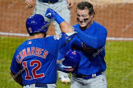 Chicago Cubs' Anthony Rizzo, right, celebrates with Kyle Schwarber (12) as he returns to the dugout after hitting a two run home run off Pittsburgh Pirates relief pitcher Sam Howard during the eighth inning of a baseball game in Pittsburgh