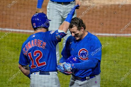 Chicago Cubs' Anthony Rizzo, right, celebrates with Kyle Schwarber (12) as he returns to the dugout after hitting a two-run home run off Pittsburgh Pirates relief pitcher Sam Howard during the eighth inning of a baseball game in Pittsburgh