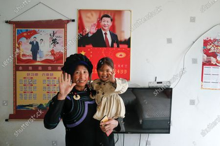Minority woman and a child wave near posters showing images of Chinese President Xi Jinping and his wife Peng Liyuan on display on a wall at her house in Xujiashan village in Ganluo County, southwest China's Sichuan province on . Communist Party Xi's smiling visage looks down from the walls of virtually every home inhabited by members of the Yi minority group in a remote corner of China's Sichuan province. Xi has replaced former leader Mao Zedong for pride of place in new brick and concrete homes built to replace crumbling traditional structures in Sichuan's Liangshan Yi Autonomous Prefecture, which his home to about 2 million members of the group