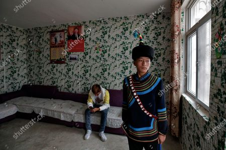 Yi ethnic minority member stands inside his house displaying posters of Chinese President Xi Jinping and his wife Peng Liyuan, in Xujiashan village in Ganluo County, southwest China's Sichuan province, on . Communist Party Xi's smiling visage looks down from the walls of virtually every home inhabited by members of the Yi minority group in a remote corner of China's Sichuan province. Xi has replaced former leader Mao Zedong for pride of place in new brick and concrete homes built to replace crumbling traditional structures in Sichuan's Liangshan Yi Autonomous Prefecture, which his home to about 2 million members of the group