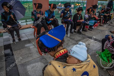 (09/50) A Yi ethnic minority woman who was relocated from remote area sews with a baby sleeping on her during a government-organised media tour at Chengbei Gang'en community, in Yuexi County, China's Sichuan Province, 11 September 2020. Over the past four decades, China says it has lifted more than 800 million people out of poverty, a phenomenon that has been described as 'unmatched in human history' by politicians such as former World Bank President Jim Yong Kim. Over the past five years, 70 million people have been the beneficiaries of poverty alleviation schemes, according to official figures. This year, the superpower is looking to do the same for a further 30 million. China's poor, rural population is largely located in the southwest, with Sichuan province being one of the country's most poverty-stricken regions. Out of the approximately 200,000 people living below the poverty line in Sichuan, almost 90 percent live in Liangshan Prefecture, which is home to the largest ethnic Yi population in the country. According to official figures, there were six million people living in poverty in Sichuan seven years ago. Under the poverty alleviation program, villagers in remote areas are relocated to towns that have been built by the state and are equipped with water and electricity, healthcare facilities and schools while providing the possibility of finding employment and leaving behind the hardship of rural life. But for many of the relocated families, the sudden transition to an urban lifestyle after generations of working and living off the land has been difficult. The open air of the fields has been replaced by small, often overcrowded urban dwellings, most of which have portraits of Chinese President Xi Jinping hanging on their walls. The relocated rural population told EPA-EFE that they did not hang the pictures up themselves. They are also concerned that their language and culture could be under threat, as the local schools only teach classes in Mandarin. Local 