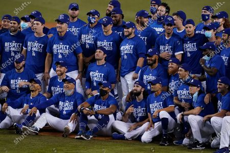 The Los Angeles Dodgers pose for a photo after the Dodgers clinched the NL West title with a 7-2 win over the Oakland Athletics in a baseball game, in Los Angeles