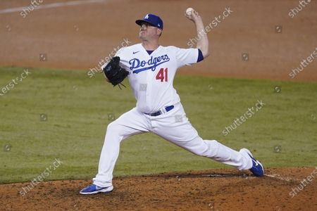Los Angeles Dodgers relief pitcher Jake McGee winds up during the ninth inning of the team's baseball game against the Oakland Athletics, in Los Angeles
