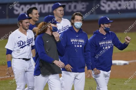 Los Angeles Dodgers gather after the Dodgers clinched the NL West title with a 7-2 win over the Oakland Athletics in a baseball game, in Los Angeles