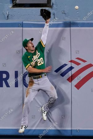Oakland Athletics center fielder Mark Canha can't make the catch on a home run by Los Angeles Dodgers' A.J. Pollock during the fourth inning of a baseball game, in Los Angeles