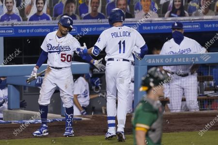 Los Angeles Dodgers' A.J. Pollock, center, celebrates with Mookie Betts, left, after his home run during the fourth inning of a baseball game against the Oakland Athletics, in Los Angeles