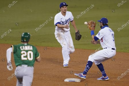 Los Angeles Dodgers shortstop Corey Seager, center, tosses the ball to second baseman Chris Taylor to put out Oakland Athletics' Mark Canha on a grounder by Jake Lamb, who was safe at first during the sixth inning of a baseball game, in Los Angeles. Lamb was safe at first