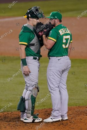 Oakland Athletics catcher Sean Murphy, left, and relief pitcher J.B. Wendelken talk on the mound after Wendelken walked two Los Angeles Dodgers, loading the bases during the seventh inning of a baseball game, in Los Angeles