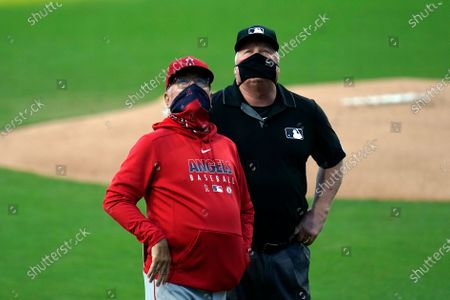 Stock Image of Los Angeles Angels manager Joe Maddon, left, looks up alongside second base umpire Bill Miller as they wait for lights to be turned on at Petco Park during the first inning of a baseball game against the San Diego Padres, in San Diego