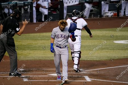Texas Rangers' Anderson Tejeda, middle, takes off his batting helmet after striking out as Arizona Diamondbacks catcher Carson Kelly, right, heads back to the dugout and umpire John Libka (84) calls the final strike during the first inning of a baseball game, in Phoenix
