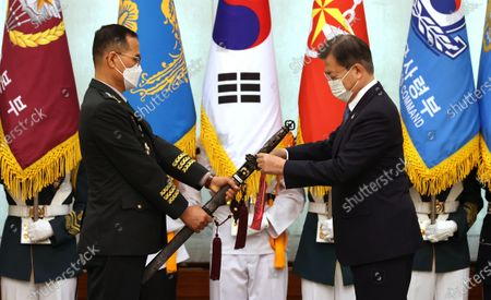 Stock Photo of South Korea's President Moon Jae-in (R) ties a tassel onto the sword of Gen. Nam Yeong-shin, new Army Chief of Staff, during his inauguration ceremony at the presidential office Cheong Wa Dae in Seoul, South Korea, 23 September 2020. The traditional Korean sword, Sam Jeong Geom, or the Three Spirits Sword, represents the defense of the country, unification and prosperity, as well as the Army, Navy and Air Force. The tassel bears the recipient's post, inauguration date and the president's name in Korean.