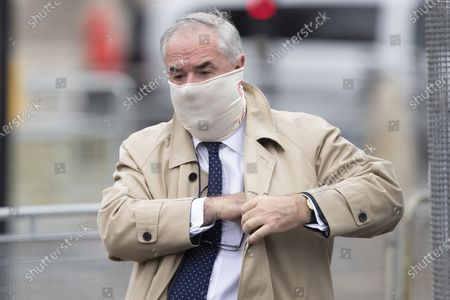 Former Attorney General Geoffrey Cox wears a mask as he arrives at The Houses of Parliament.