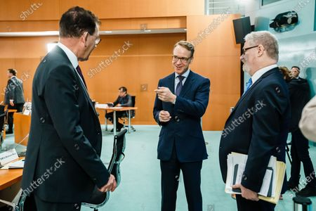 Stock Picture of German Minister of Economic Cooperation and Development Gerd Mueller (L), President of the Central Bank of Germany Jens Weidmann (C) and economy and finance policy advisor of the German Chancellor Lars-Hendrik Roeller (R) talk