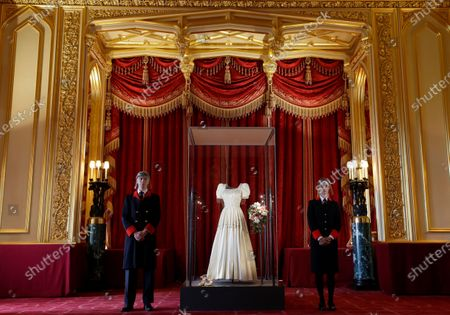 Two wardens stand by Princess Beatrice's wedding dress, designed by the renowned British fashion designer Sir Norman Hartnell and loaned to by Queen Elizabeth II, on display at Windsor Castle in Windsor, England, . Princess Beatrice's wedding dress, first worn by Queen Elizabeth II in the 1960s, will go on public display at Windsor Castle from Thursday, Sept. 24. The display can be seen in the Semi-State Rooms, which open to the public for their annual winter opening from Thursday and are among the most richly decorated interiors in the Castle