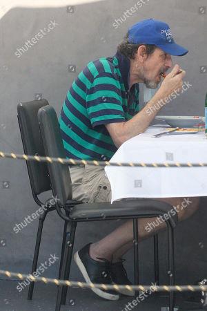 Howard Rosenman is seen eating at a restaurant.