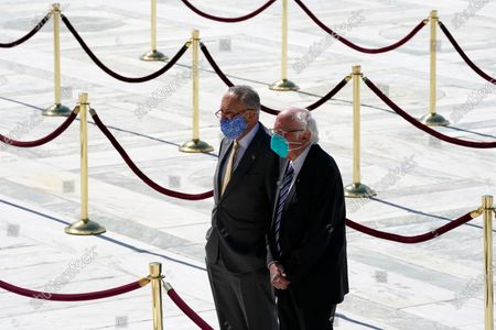 Stock obrázek na téma Senate Minority Leader Chuck Schumer, D-N.Y., and Sen. Bernie Sanders, I-Vt., pay respects as Justice Ruth Bader Ginsburg lies in repose under the Portico at the top of the front steps of the U.S. Supreme Court building, in Washington. Ginsburg, 87, died of cancer on Sept. 18