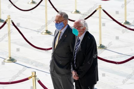 Arkistokuva kohteesta United States Senate Minority Leader Chuck Schumer (Democrat of New York), and United States Senator Bernie Sanders (Independent of Vermont), pay respects as Justice Ruth Bader Ginsburg lies in repose under the Portico at the top of the front steps of the U.S. Supreme Court building, in Washington. Ginsburg, 87, died of cancer on Sept. 18.