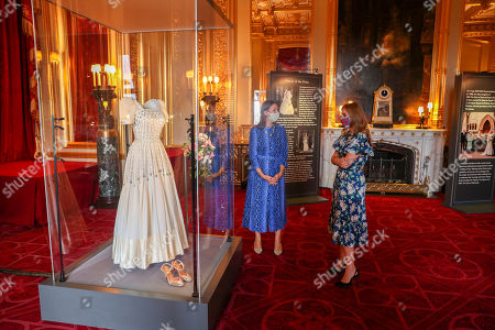 Stock Picture of Princess Beatrice alongside her wedding dress, talks with Royal Collection Trust curator Caroline de Guitut, ahead of it going on public display at Windsor Castle from Thursday. The Sir Norman Hartnell gown, first worn by the Queen in the 1960s, was loaned to Beatrice by her grandmother for her secret, low-key wedding to Edoardo Mapelli Mozzi in July.