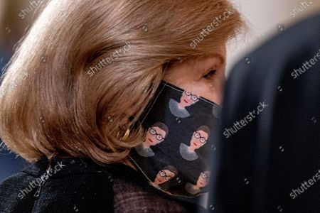 Supreme Court reporter Nina Totenberg wears a face mask with depictions of Justice Ruth Bader Ginsburg on it during a private ceremony for Justice Ginsburg at the Supreme Court in Washington, . Ginsburg, 87, died of cancer on Sept. 18