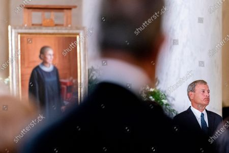 Chief Justice of the United States John Roberts asks for a moment of silence while speaking during a private ceremony for Justice Ruth Bader Ginsburg at the Supreme Court in Washington, . Ginsburg, 87, died of cancer on Sept. 18. At left is a 2016 portrait of Ginsburg by artist Constance P. Beaty