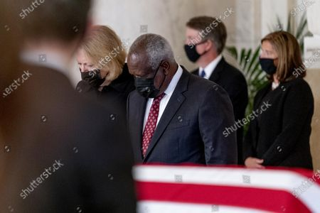Stock Image of From left, Virginia Thomas, her husband Justice Clarence Thomas, Justice Brett Kavanaugh and his wife Ashley Kavanaugh, stand during a private ceremony for Justice Ruth Bader Ginsburg at the Supreme Court in Washington,. Ginsburg, 87, died of cancer on Sept. 18.