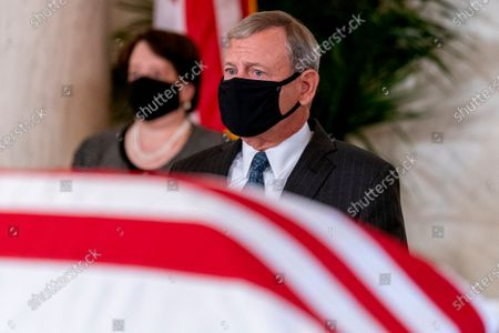 Chief Justice of the United States John Roberts, center, and Associate Justice Elena Kagan, left, sit in front of the flag-draped casket of Justice Ruth Bader Ginsburg during a private ceremony at the Supreme Court in Washington,. Ginsburg, 87, died of cancer on Sept. 18.