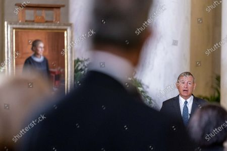 Stock Photo of Chief Justice of the United States John Roberts speaks in front of a 2016 portrait of Justice Ruth Bader Ginsburg during a private ceremony at the Supreme Court in Washington,. Ginsburg, 87, died of cancer on Sept. 18. Also pictured is Justice Elena Kagan, right.
