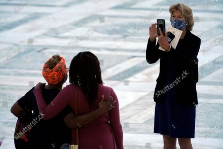 Sen. Lisa Murkowski, R-Alaska, takes a photo for mourners paying respects as Justice Ruth Bader Ginsburg lies in repose under the Portico at the top of the front steps of the US Supreme Court building in Washington, DC, USA, 23 September 2020. Thousands of mourners are expected to pay their respects to Justice Ginsburg, who will lay in repose outside the high court for two days.