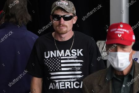 """Supporter of President Donald Trump wears a t-shirt that reads """"Unmask America"""" at a campaign rally held by Vice President Mike Pence, at Lanconia Municipal Airport in Gilford, N.H"""