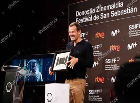 Spanish script writer Jose Mari Goenaga poses with the VI EZAE Award for his film 'La Trinchera Infinta' (lit. 'The Never Ending Trench') during the 68th edition of the San Sebastian International Film Festival, in San Sebastian, Spain, 23 September 2020.