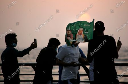 Saudis watch the sunset as they wave a flag with pictures of Saudi King Salman, right, and Crown Prince Mohammed bin Salman during a celebration marking National Day to commemorate the unification of the country as the Kingdom of Saudi Arabia, in Jiddah, Saudi Arabia