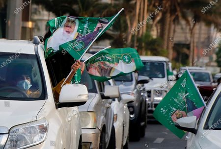 Saudis wave national flags with pictures of Saudi King Salman, right, and Crown Prince Mohammed bin Salman during celebrations marking National Day to commemorate the unification of the country as the Kingdom of Saudi Arabia, in Jiddah, Saudi Arabia