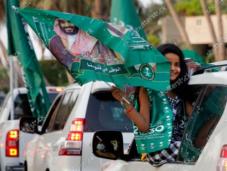 Saudi girls waves wave a national flag with picture of Saudi Crown Prince Mohammed bin Salman during celebrations marking National Day to commemorate the unification of the country as the Kingdom of Saudi Arabia, in Jiddah, Saudi Arabia