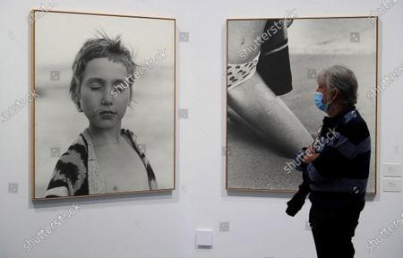 Stock Image of A man looks at the photographs 'Girl on the Beach, Ukraine, 2001' (L) and 'Knee in the sand , Ukraine, 2001' (R) taken by German photographer Frauke Eigen, on display as part of an exhibition, titled 'Between Art and Fashion. Photographs from the Collection of Carla Sozzani' at the CentroCentro Cibeles in Madrid, Spain, 23 September 2020. The exhibition featuring works from the photography collection of Italian book and magazine editor, gallerist, and businesswoman Carla Sozzani runs from 23 September 2020 to 10 January 2021.
