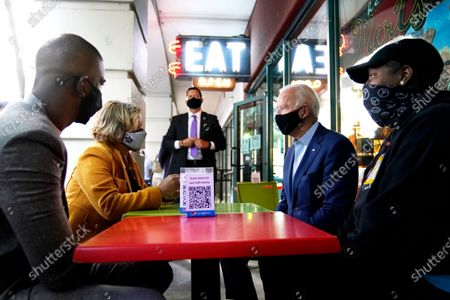 Democratic presidential candidate former Vice President Joe Biden talks with Charlotte, N.C., Mayor Vi Lyles, second from left, NBA player Chris Paul, left, and daughter of the owners of the restaurant, Tia Bozzell, right, at Mert's Heart & Soul Restaurant in Charlotte, N.C