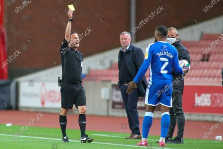 David Webb Referee shows Ryan Jackson of Gillingham (2) a yellow card during the EFL Cup match between Stoke City and Gillingham at the Bet365 Stadium, Stoke-on-Trent