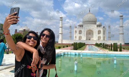 Visitors take slefies with the Taj Mahal in Agra, India, Sept. 23, 2020.   India's iconic monument of love - Taj Mahal, which was closed on March 17 amid the COVID-19 pandemic, was reopened Monday to tourists, officials said.