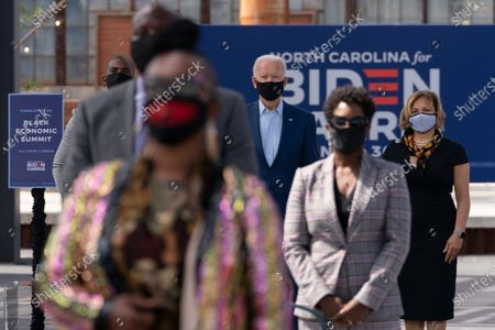 Democratic presidential candidate former Vice President Joe Biden poses for a photo practicing social distancing after speaking during a Biden for President Black economic summit at Camp North End in Charlotte, N.C., . At right is Charlotte, N.C., mayor Vi Lyles and left is NBA player Chris Paul