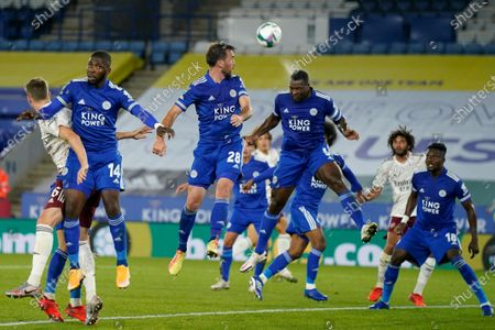 Leicester's Wes Morgan, center right, clears a corner shot during the English League Cup 3rd round soccer match between Leicester City and Arsenal at the King Power Stadium in Leicester, England