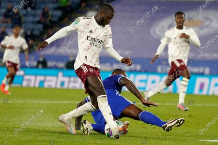 Leicester's Wes Morgan, on the ground, tries to block a shot from Arsenal's Nicolas Pepe during the English League Cup 3rd round soccer match between Leicester City and Arsenal at the King Power Stadium in Leicester, England