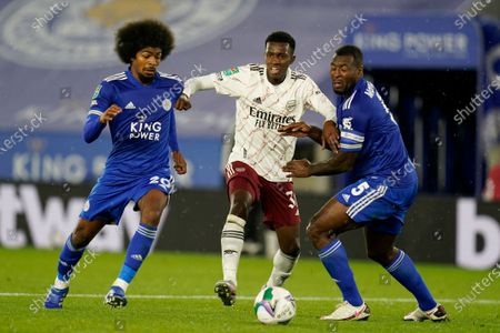 Arsenal's Eddie Nketiah vies for the ball with Leicester's Hamza Choudhury, left, and Wes Morgan, right, during the English League Cup 3rd round soccer match between Leicester City and Arsenal at the King Power Stadium in Leicester, England