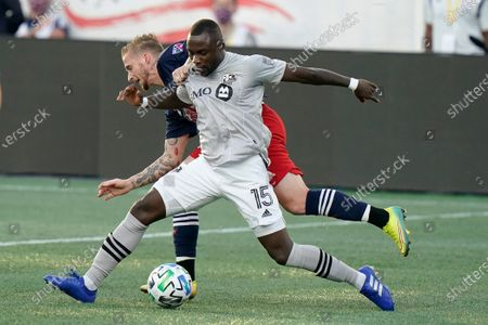 Stock Picture of Montreal Impact's Zachary Brault-Guillard, right, and New England Revolution's Alexander Buttner, left, vie for control of the ball during the first half of an MLS soccer match, in Foxborough, Mass