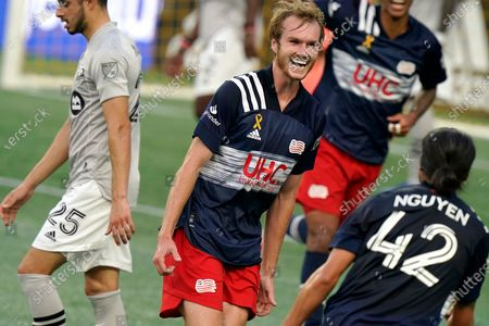 New England Revolution's Henry Kessler, center, celebrates with teammate Lee Nguyen, right, after scoring in the first half of an MLS soccer match as Montreal Impact's Emanuel Maciel (25) steps away, in Foxborough, Mass